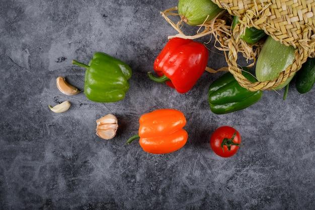 Poivrons de couleur verte, rouge et orange dans un panier rustique.