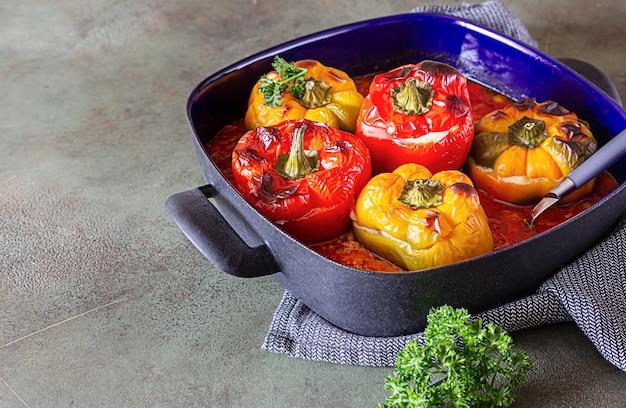 Poivrons doux farcis cuits au four avec du poulet ou de la dinde, du maïs et des herbes dans un plat profond.
