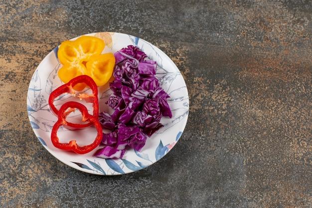 Poivrons doux tranchés et chou rouge finement haché dans l'assiette, sur la surface en marbre