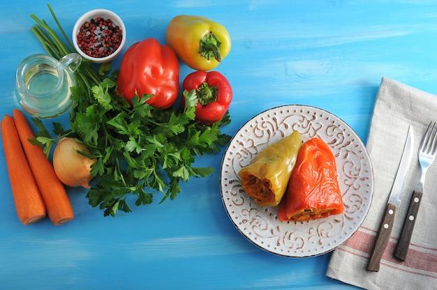 Poivrons farcis de carottes et d'herbes et d'ingrédients sur une surface en bois bleue