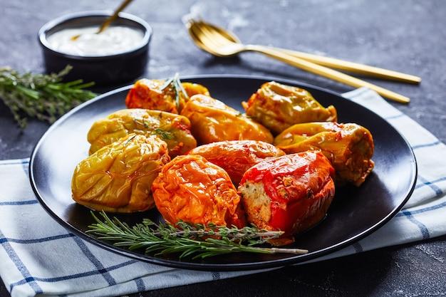 Poivrons farcis classiques avec riz, boeuf haché et porc à la sauce tomate, romarin et thym sur une plaque noire avec de la crème sure