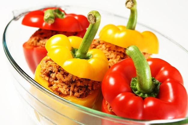 Un poivrons farcis jaunes et rouges non cuits servis dans un verre résistant à la chaleur