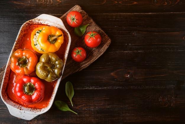 Poivrons farcis maison. avec une garniture de basilic, d'épinards, de fromage et d'épices. avec sauce de tomates fraîches faites maison. fait dans un style rustique.