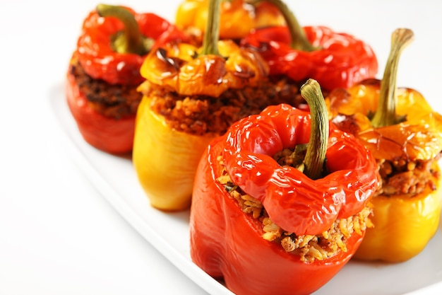 Poivrons farcis rouges et jaunes cuits au four et servis sur une assiette blanche