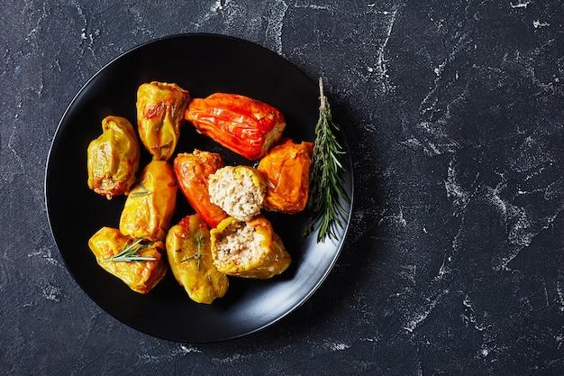 Poivrons farcis sains avec riz, boeuf haché et porc à la sauce tomate, romarin et thym sur une plaque noire