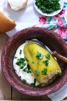 Poivrons farcis servis avec de la crème sure et du pain, un plat traditionnel de différentes nations.