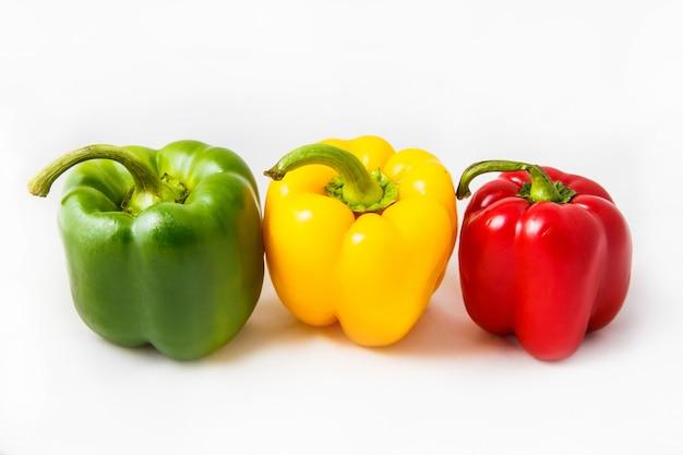Poivrons frais trois doux poivrons rouges, jaunes et verts isolés sur fond blanc.