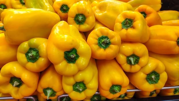 Poivrons jaunes en gondole de supermarché.