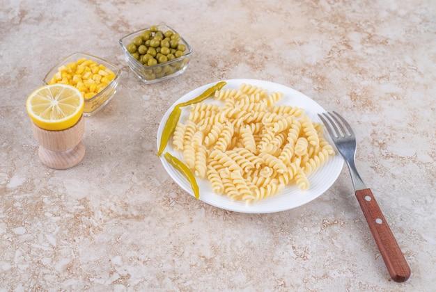 Poivrons marinés décorant des pâtes cuites, avec des bols de petits pois, du maïs et un citron tranché sur une surface en marbre.