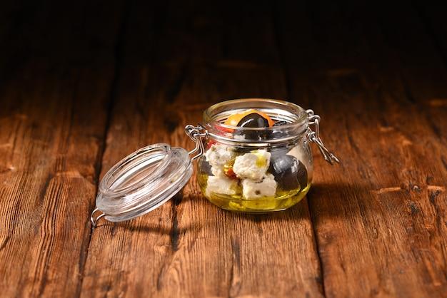 Poivrons et olives marinés au fromage feta dans un bocal de rangement sur la table en bois