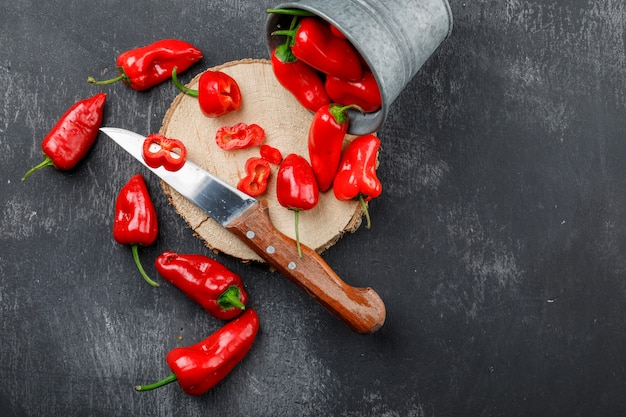 Poivrons rouges épars avec pièce en bois, couteau dans un mini seau sur mur gris grungy, pose à plat.