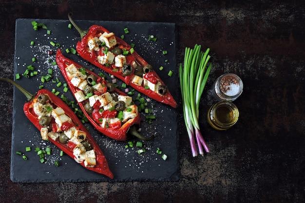 Poivrons rouges farcis de feta et d'olives. paprika au four aux olives et fromage blanc. la nourriture végétarienne. régime céto.