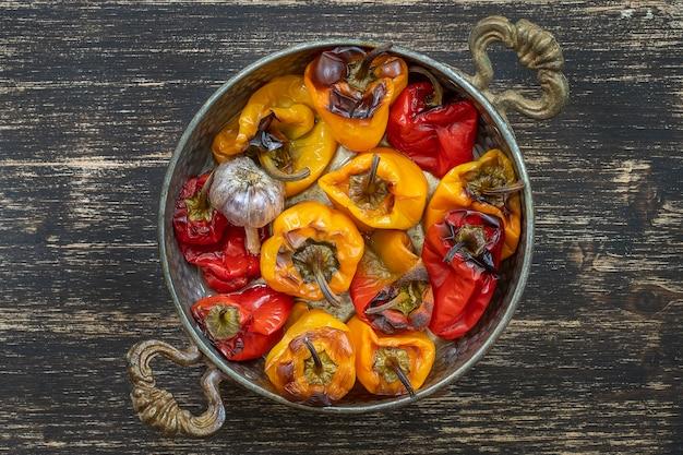 Poivrons rouges et jaunes au four. poivrons dans un plat allant au four sur une table en bois. un plat végétarien sain et délicieux. gros plan, vue de dessus