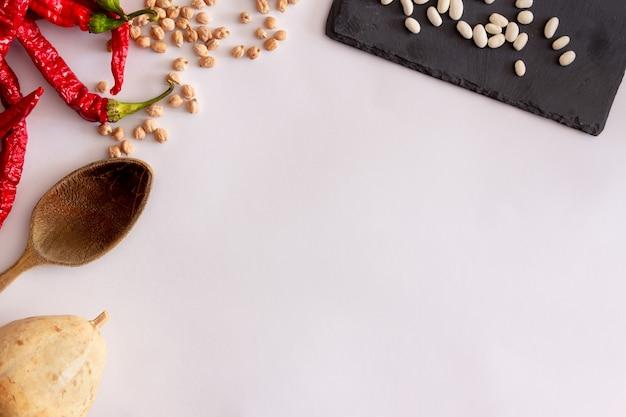Poivrons rouges séchés citrouille haricots louche en bois sur ardoise et pois chichescuisine méditerranéenne copy space