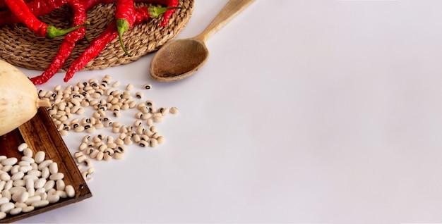 Poivrons rouges sur une surface en osier citrouille séchée à la louche en bois et divers types de haricots méditerranéens