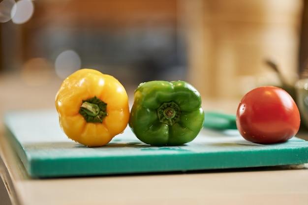 Poivrons et tomates juteux frais sur le dessus du conseil de cuisine