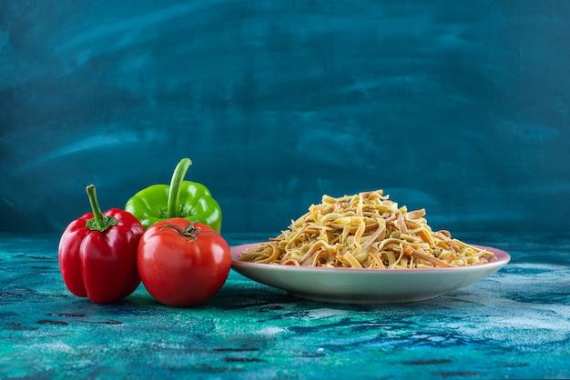 Poivrons, tomates et nouilles dans une assiette, sur la table bleue.