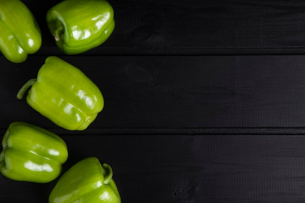 Poivrons verts entiers placés sur une table sombre en bois. photo de haute qualité