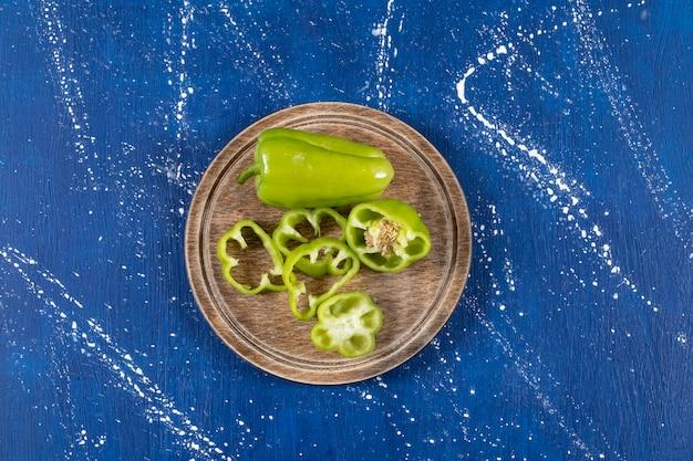 Poivrons verts et tranches sur planche de bois sur une surface en marbre.