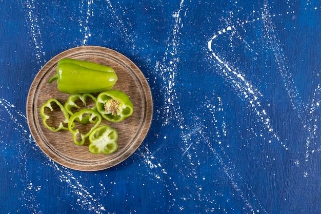 Poivrons verts et tranches sur planche de bois sur une surface en marbre
