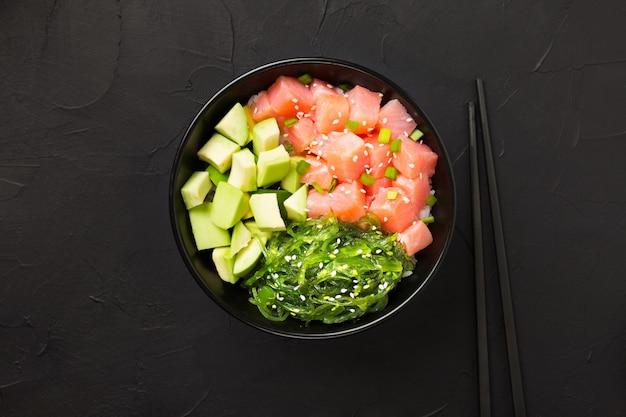 Poke au poisson rouge, avocat et algues vertes décorées avec des oignons verts