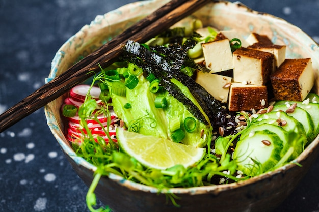 Poke bol avec avocat, riz noir, tofu fumé, légumes, pousses
