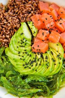 Poke bol. ingrédients: saumon, avocat, riz brun, algues.