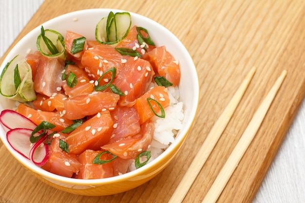 Poke hawaïen au saumon et graines de sésame, riz bouilli, concombre frais, radis et oignons verts dans un bol avec des baguettes en bois sur une planche à découper en bois