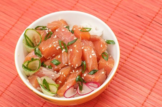 Poke hawaïen au saumon et graines de sésame, riz bouilli, concombre frais, radis et oignons verts dans un bol sur la serviette en bambou rouge