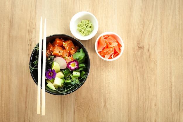 Poke salade au saumon dans un bol à côté de wasabi et gingembre