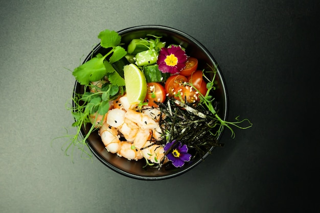 Poke salade aux crevettes dans un bol. ingrédients crevettes, épinards blanchis, tomates cerises, riz, concombre, sauce soja-gingembre, sauce épicée, nori, sésame, citron vert, coriandre. concept de salade de fruits de mer asiatique.