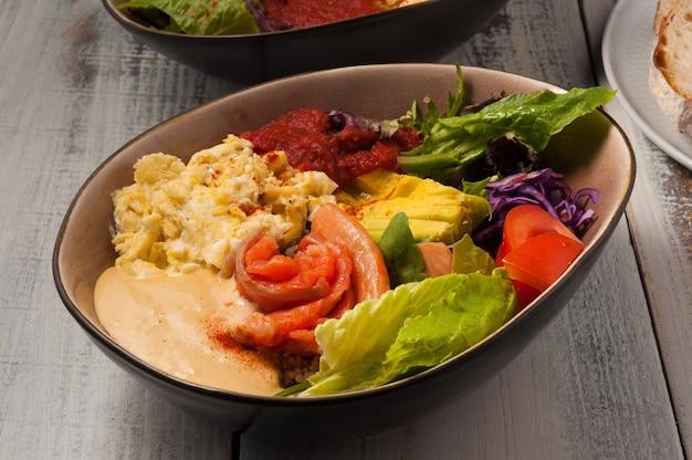 Poke savoureux au saumon, avocat, omelette et légumes