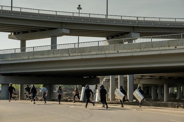 La police anti-émeute avec des boucliers courant pour les jeunes contrevenants sous les ponts pour les attraper et les arrêter