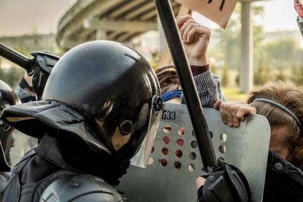 La police anti-émeute dans des casques tenant des boucliers et des matraques et poussant la foule de manifestants tout en les arrêtant dans la rue