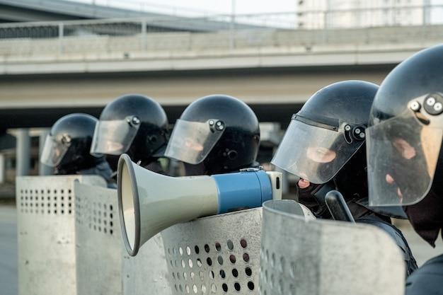 Policier en casque anti-émeute debout parmi des collègues avec des boucliers anti-émeute et parlant dans un mefaphone tout en neutralisant les terroristes