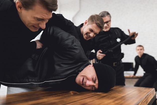 Le policier a pressé le criminel contre la table et le tient.