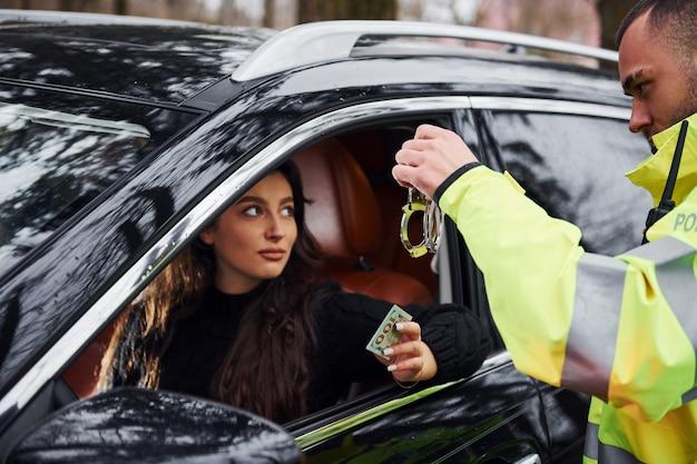 Un policier en uniforme vert et avec des menottes refuse de prendre un pot-de-vin d'une femme dans un véhicule.