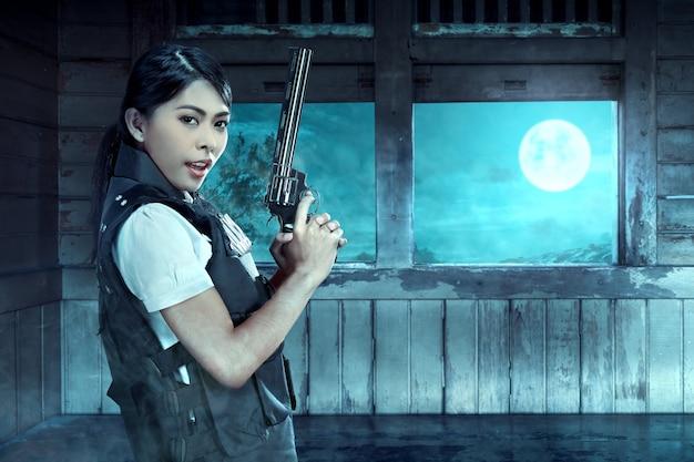 Policière asiatique avec le pistolet sur sa main veille à l'intérieur du vieux wagon