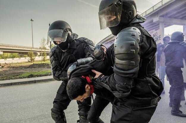 Des policiers anti-émeute qualifiés dans des casques tenant la main d'un rebelle derrière son dos lors de l'arrestation de personnes lors d'un rassemblement
