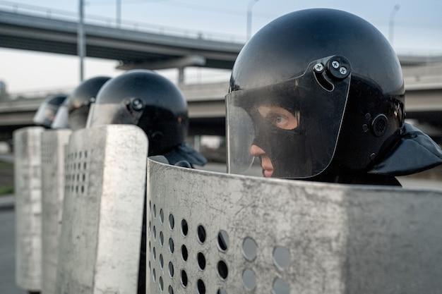 Des policiers portant des casques et des boucliers anti-émeute se tiennent en rang et font face à des manifestations en ville