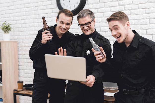 Les policiers regardent l'ordinateur portable ensemble.