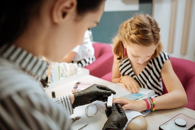 Polir les ongles. nail artiste professionnel aux cheveux noirs polissant les ongles de sa jolie cliente adolescente