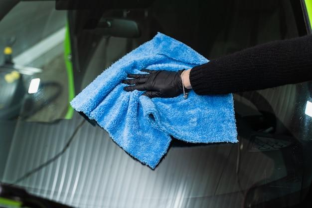 Polir la vitre de la voiture avec un chiffon en microfibre bleu.