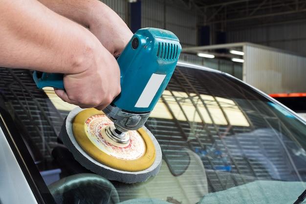 Polissage de verre de voiture avec la machine de tampon de puissance.