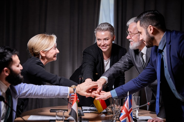 Des politiciens heureux signent un accord, gardent les mains ensemble, célèbrent, font du bon travail ensemble