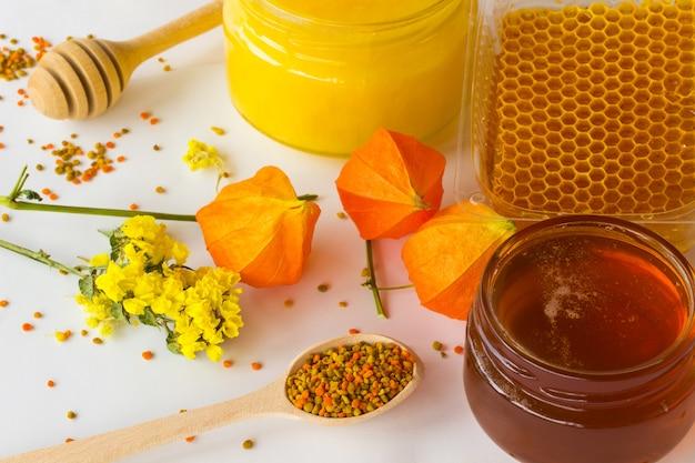 Pollen dans une cuillère en bois, deux pots de miel foncé et clair.