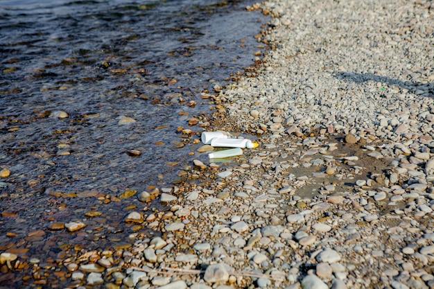 Pollution de la rivière près du rivage, ordures près de la rivière, déchets alimentaires en plastique, contribuant à la pollution