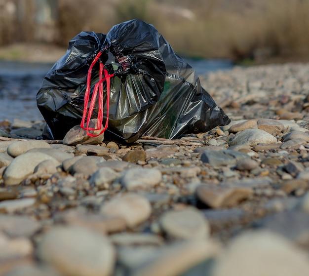 Pollution de la rivière près du rivage, sac à ordures près de la rivière, déchets alimentaires en plastique, contribuant à la pollution