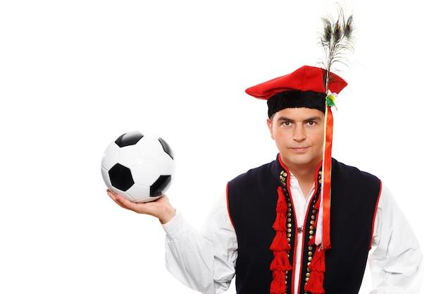 Un polonais en tenue traditionnelle avec un ballon de football