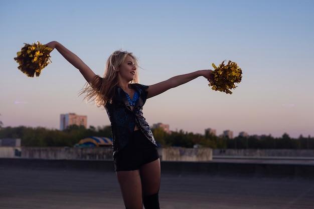 Pom-pom girl à pompons dansant en plein air sur le toit au coucher du soleil